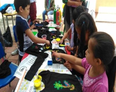 Niñas y niños de primera infancia creando con colores sobre tela.